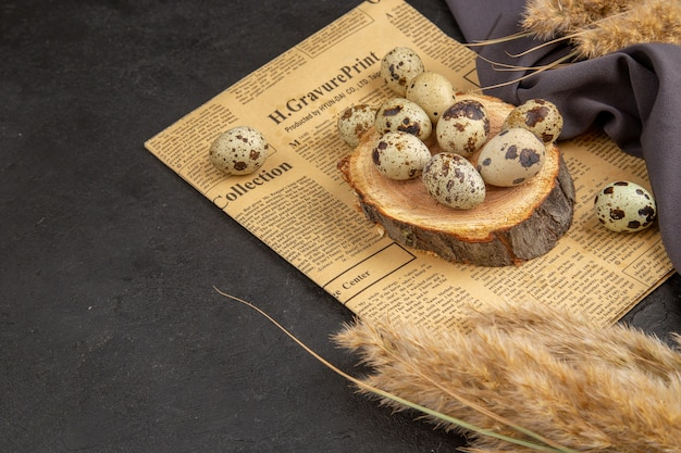 Seitenansicht von bio-eiern auf einem holzbrett auf einem alten schwarzen handtuch mit zeitungsspitze auf dunkler oberfläche