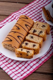 Seitenansicht von biskuitkuchen mit schokolade auf einem weißen teller, der mit einer tasse tee serviert wird