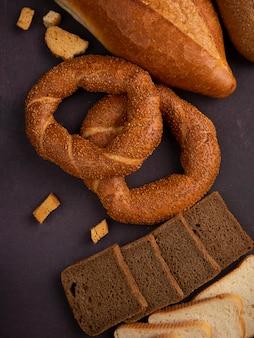 Seitenansicht von broten als bagel-baguette, geschnittener roggen und weißbrot auf kastanienbraunem hintergrund