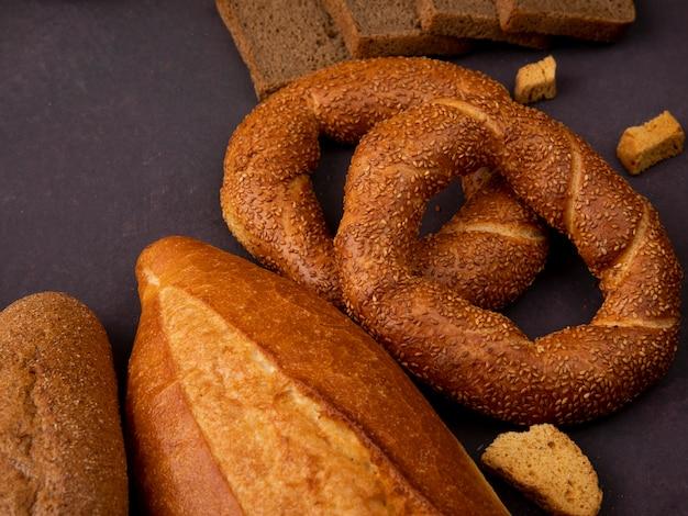 Seitenansicht von broten als sandwichbrot-baguette-bagel auf kastanienbraunem hintergrund mit kopienraum