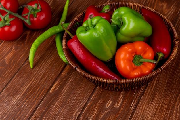 Seitenansicht von buntem paprika des frischen gemüses rote chilischoten in einem weidenkorb auf rustikalem holztisch