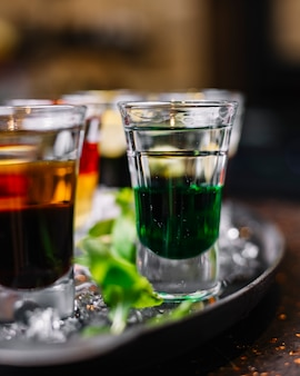 Seitenansicht von bunten cocktails in schnapsgläsern