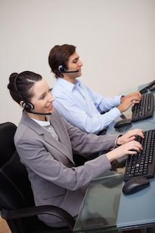 Seitenansicht von call-center-agenten, die ihre arbeit erledigen