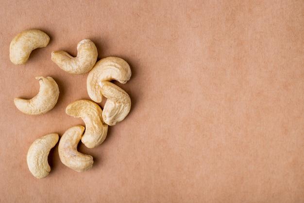 Seitenansicht von cashewnüssen auf altem papierbeschaffenheitshintergrund mit kopienraum