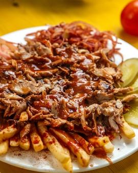 Seitenansicht von chiken döner kebab auf dem teller mit brot pommes frites tomaten zwiebeln gurken und sauce
