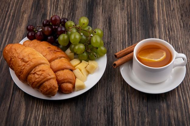 Seitenansicht von croissants mit trauben und käsescheiben im teller mit tasse heißem wirbel mit zimt auf untertasse auf hölzernem hintergrund
