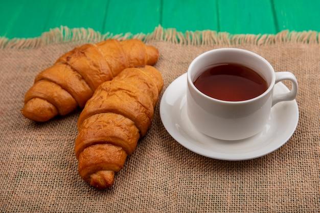 Seitenansicht von croissants und tasse tee auf untertasse auf sackleinen auf grünem hintergrund
