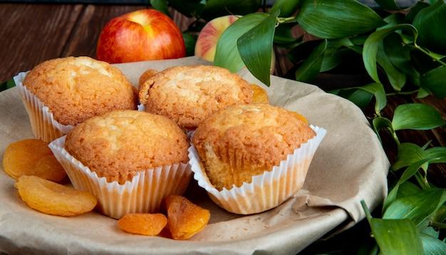Seitenansicht von cupcakes mit getrockneten pflaumen in teller und pfirsichen auf holztisch mit blättern verziert
