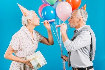 Seitenansicht von den älteren Paaren, die einander Schlagparteihorn auf blauem Hintergrund betrachten