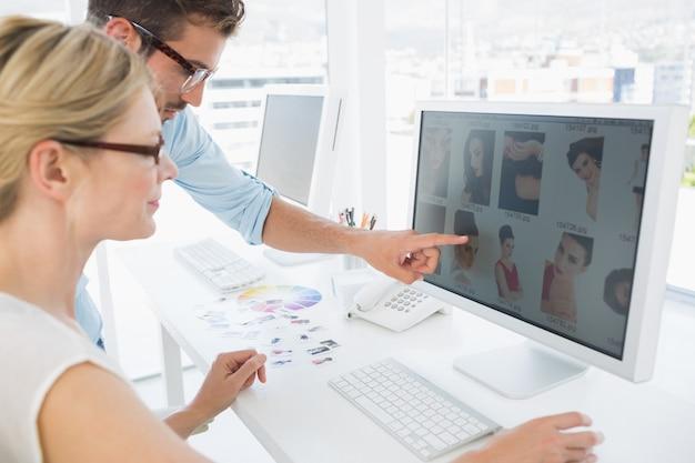 Seitenansicht von den bildeditoren, die an computer in einem hellen büro arbeiten