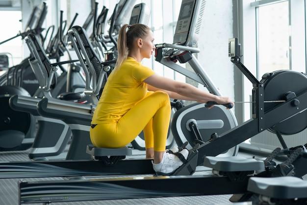 Seitenansicht von den jungen frauen des sitzes, die rudermaschine im fitnessstudio verwenden