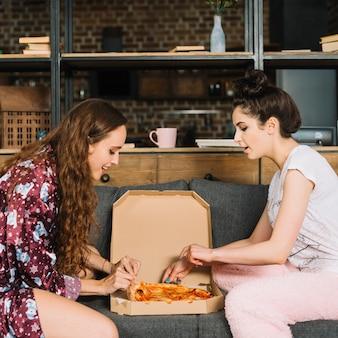 Seitenansicht von den jungen frauen, die pizzascheiben vom kasten nehmen