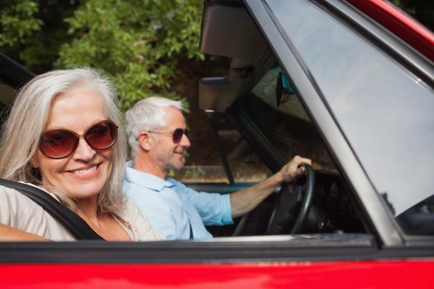 Seitenansicht von den lächelnden reifen paaren, die roten cabriolet fahren