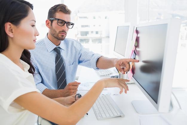 Seitenansicht von den zufälligen bildeditoren, die an computer arbeiten