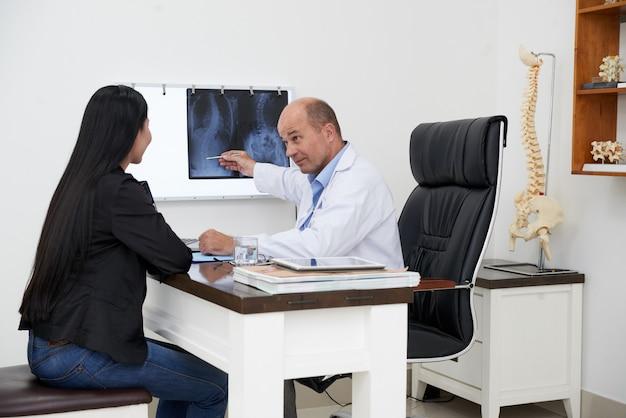 Seitenansicht von doktor zeigend auf dornkrümmungs-röntgenstrahl, der dem weiblichen patienten die krankheitsspezifikation declinnig ist