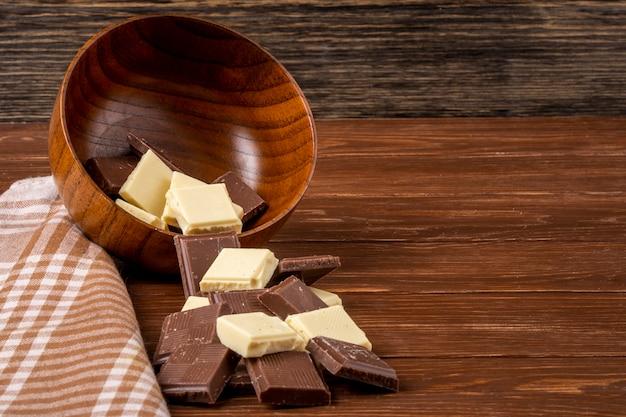 Seitenansicht von dunklen und weißen schokoladenstücken, die von einer holzschale auf rustikalem hintergrund mit kopienraum verstreut sind