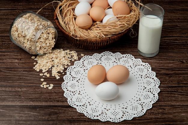 Seitenansicht von eiern auf papierdeckchen mit haferflocken, die aus glas und milch auf hölzernem hintergrund verschütten