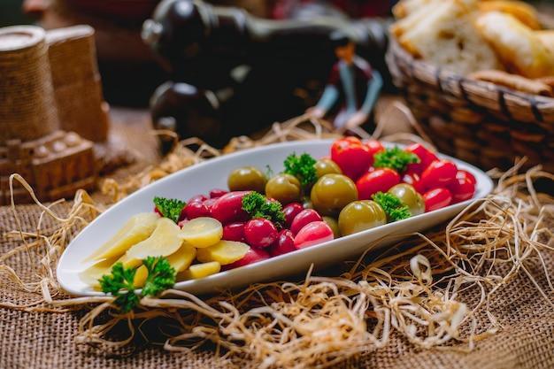Seitenansicht von eingelegten gemüsetomatengurken und hartriegel in einer platte auf strohhintergrund