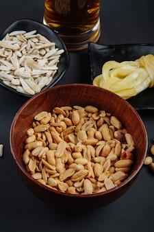 Seitenansicht von erdnüssen in einer holzschale und in sonnenblumenkernen mit streichkäse und einem becher bier auf schwarz