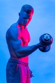 Seitenansicht von fit hemdlosem mann mit gewichten