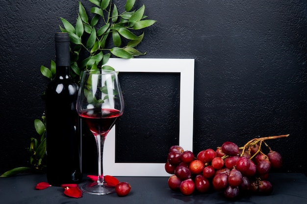 Seitenansicht von flasche und glas rotwein mit traubenrahmen und blättern mit blütenblättern auf schwarz mit kopienraum
