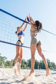 Seitenansicht von frauen, die beim spielen von volleyball nach ball über netz greifen