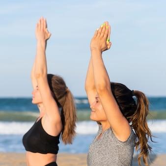 Seitenansicht von frauen, die yoga zusammen am strand tun