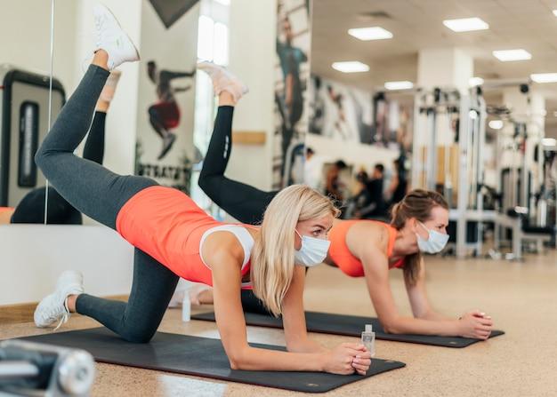 Seitenansicht von frauen mit medizinischen masken, die zusammen im fitnessstudio trainieren