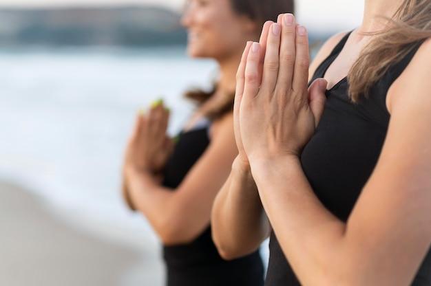 Seitenansicht von freunden, die yoga am strand tun