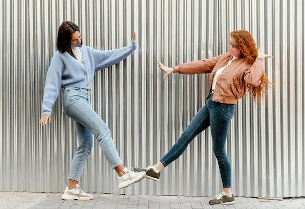 Seitenansicht von freundinnen mit gesichtsmasken im freien, die füße berühren