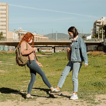 Seitenansicht von freundinnen mit gesichtsmasken im freien, die knöchel berühren