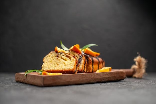 Seitenansicht von frisch gebackenen weichen kuchenscheiben auf hölzernem schneidebrett auf dunklem tisch