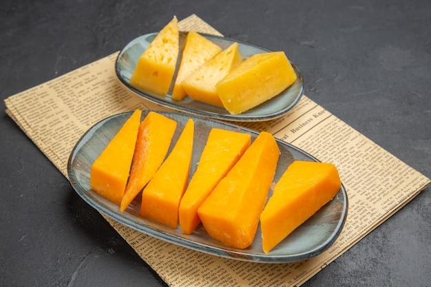 Seitenansicht von frischem verschiedenem geschnittenem käse, der auf blauen tellern auf einer alten zeitung auf schwarzem hintergrund serviert wird