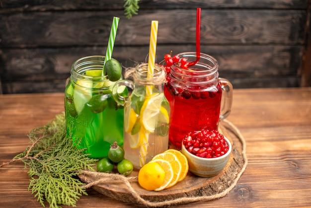 Seitenansicht von frischen bio-säften in flaschen, serviert mit tuben und früchten auf einem holzbrett