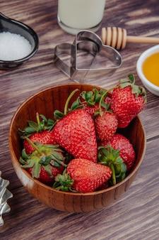 Seitenansicht von frischen reifen erdbeeren in einer holzschale mit ausstechformen und honig auf rustikalem