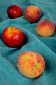 Seitenansicht von frischen reifen nektarinen und pfirsichen, die auf blauem stoff verstreut sind