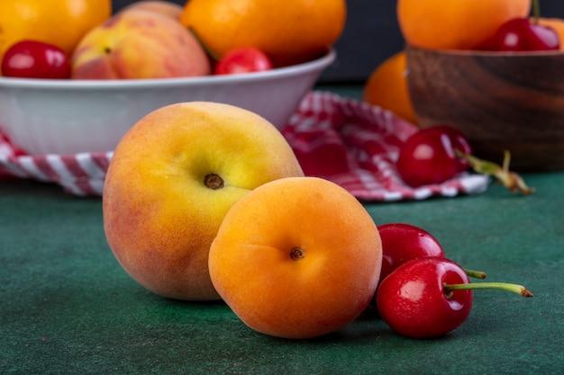 Seitenansicht von frischen reifen pfirsichen mit roten kirschen auf dunkelgrün