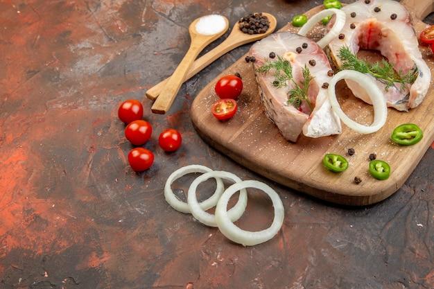 Seitenansicht von frischen rohen fischen und paprika-zwiebelgrün-tomaten auf holzschneidebrett auf der linken seite auf gemischter farboberfläche