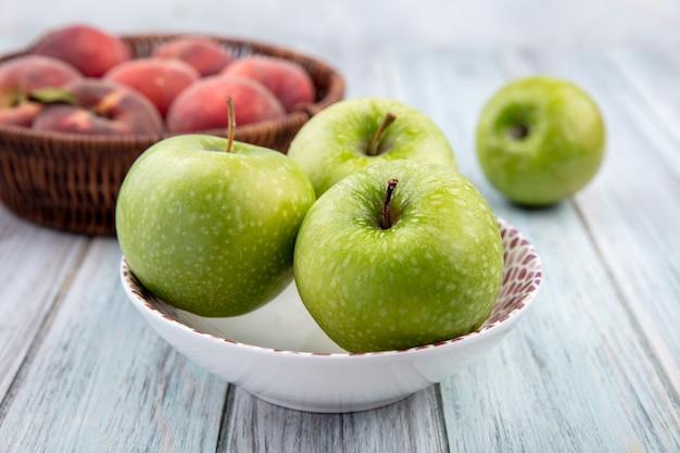 Seitenansicht von frischen und bunten früchten wie äpfeln auf einer schüssel und pfirsichen auf einem eimer auf grauer holzoberfläche