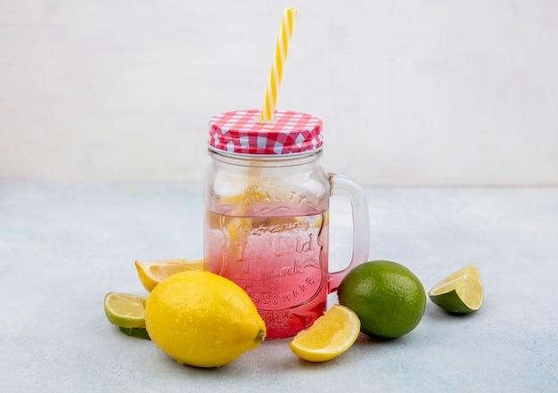 Seitenansicht von frischen und bunten zitronen mit wasser in einem glas auf weißer oberfläche