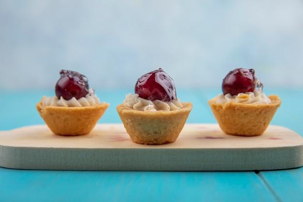 Seitenansicht von fruchtigen cupcakes auf schneidebrett auf blauer oberfläche und grauem hintergrund
