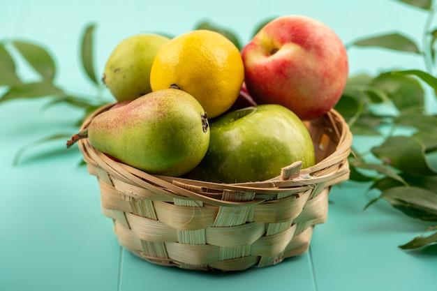 Seitenansicht von früchten als birnen-zitronen-apfel-pfirsich im korb mit blättern auf blauem hintergrund