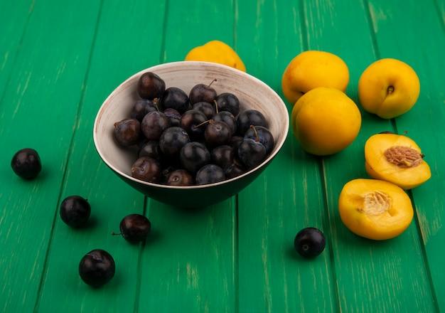 Seitenansicht von früchten als schlehenbeeren in schüssel und aprikosen mit halbem schnitt auf grünem hintergrund