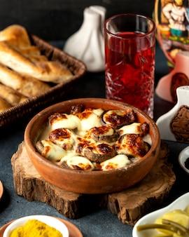 Seitenansicht von gebackenen pilzen mit käse in einer tonschale