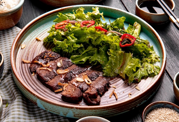 Seitenansicht von gebratenem rindfleisch mit salat und rotem chili auf einem teller auf holz