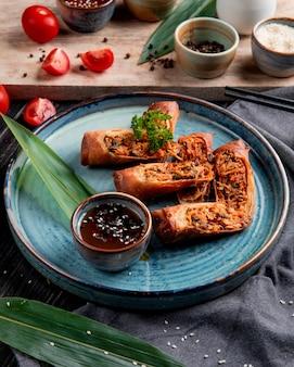 Seitenansicht von gebratenen frühlingsrollen mit huhn und gemüse serviert mit sojasauce auf einem teller auf schwarz