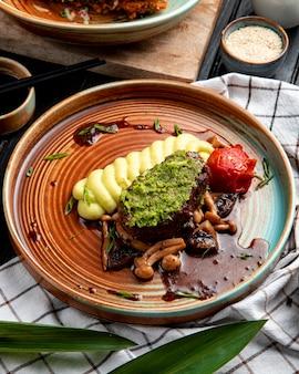 Seitenansicht von gegrilltem rindfleisch mit kartoffelpüree tomatenpilzen und avocadosauce in einem teller auf karierter tischdecke