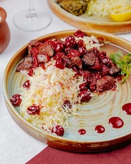 Seitenansicht von gekochtem reis mit fleisch und kirschen