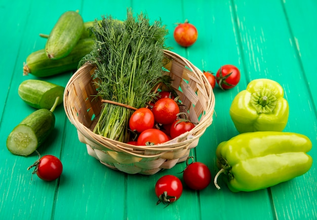 Seitenansicht von gemüse als bündel von dill und tomaten im korb mit geschnittenen gurkenpaprika und tomaten auf grün