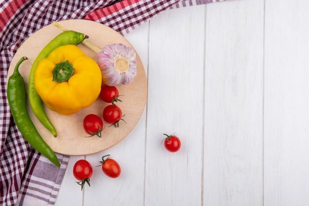Seitenansicht von gemüse als knoblauch-tomaten-pfeffer auf schneidebrett auf kariertem stoff auf holz mit kopienraum